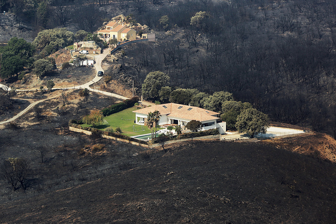 Houses surrounded by terrain scorched by wildfire near the village of Biguglia, Corsica island, France