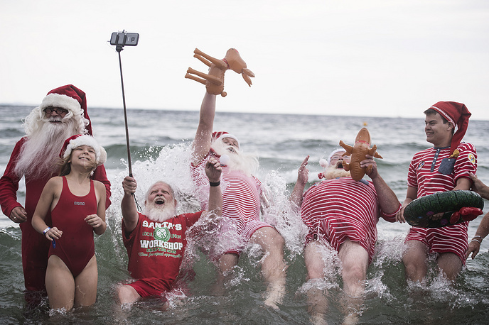 People dressed up as Santa Claus pose on the seashore as part of the annual Santa Claus World Congress near Copenhagen, Denmark, July 25