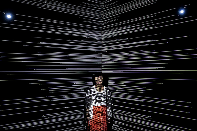 """A woman is beamed by light at an art installation titled """"Infinity Room"""" displayed during The Future of Today Exhibition at Today Art Museum in Beijing, China, August 9"""