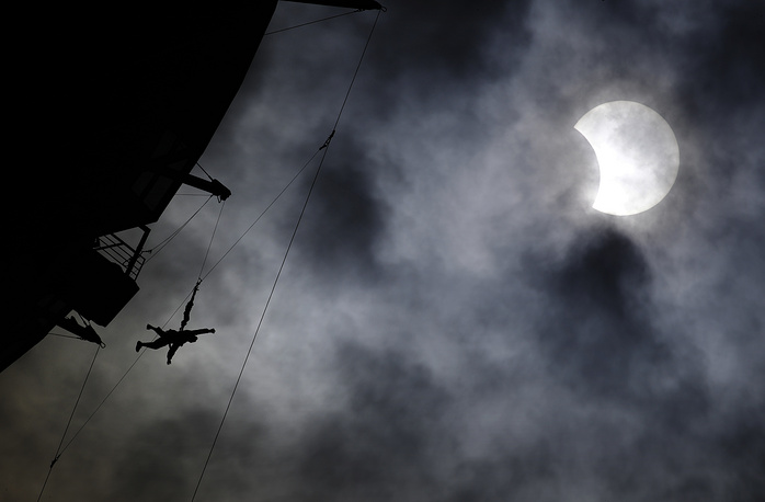 A person jumps off the top of the Stratosphere hotel and casino tower on the SkyJump ride during a partial solar eclipse in Las Vegas