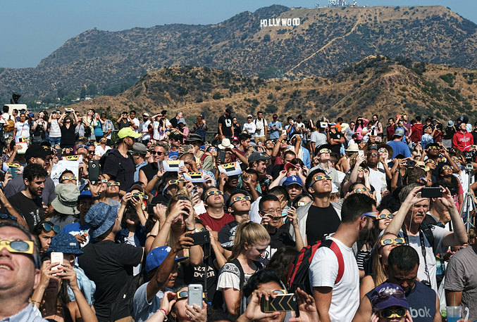 A crowd watch the solar eclipse in front of the Hollywood sign at the Griffith Observatory in Los Angeles