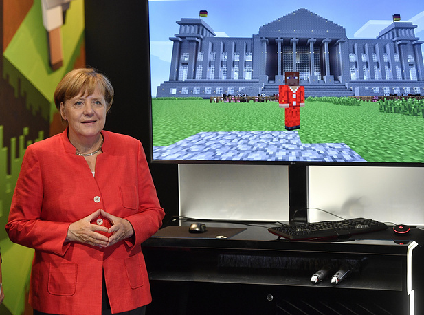 German Сhancellor Angela Merkel standing beside a Minecraft game, showing her in front of the German Reichstag, during the Gamescom fair for computer games in Cologne, Germany, August 22