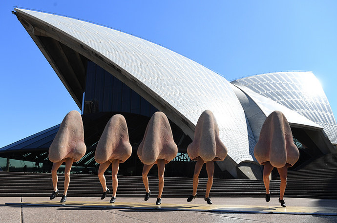 Cast members in costume from Opera Australia dance during a sneak preview from their production of Shostakovich's The Nose outside the Sydney Opera House in Sydney, Australia, August 22