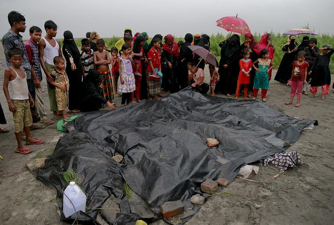Bangladeshi villagers gather around bodies of Rohingya women and children at Shah Porir Deep, in Teknak, Bangladesh