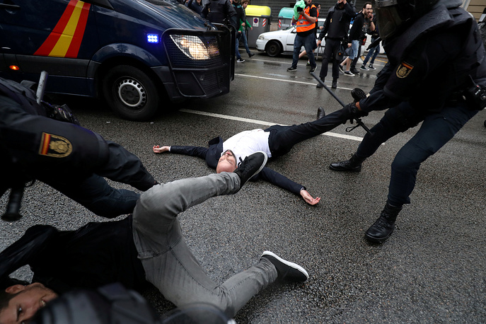 Spanish Civil Guard officers remove demonstrators outside a polling station for the banned independence referendum in Barcelona, Spain, October 1