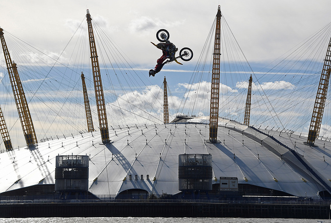 Action sports performer Travis Pastrana somersaults on his motorbike as he jumps between two barges on the River Thames with the O2 Arena sports venue seen behind, in London, Britain, October 5