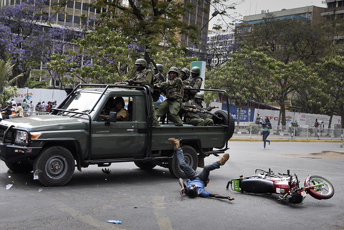 A supporter of the opposition coalition The National Super Alliance and its presidential candidate Raila Odinga hits the ground after being ran over by a police truck as he rides a motorbike during a protest in downtown Nairobi, Kenya, October 11