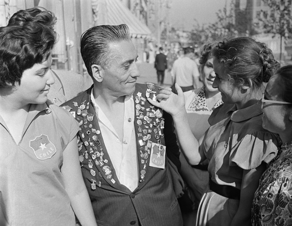 Delegate from Chile shows the pinback buttons, collected during the festival, 1957