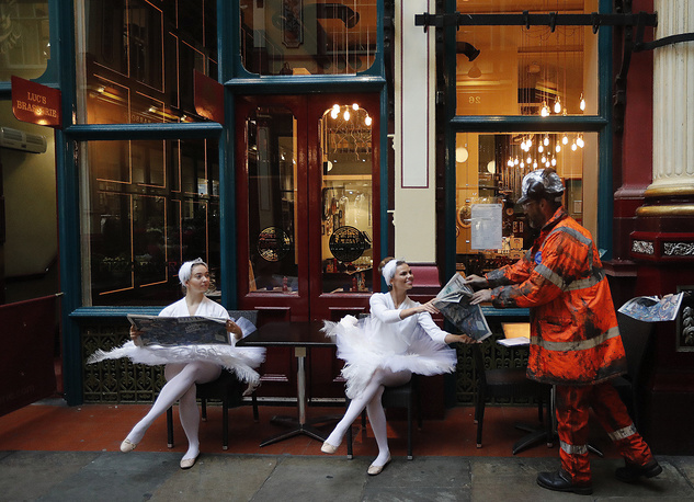 Actors dressed up sit in the streets of Leadenhall Market in London, Britain, October 24