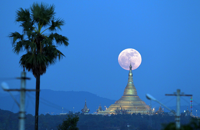 Supermoon rises behind the Uppatasanti Pagoda seen from Naypyitaw, Myanmar