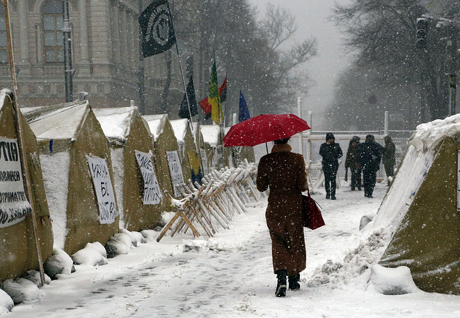 Under heavy snowfall a woman passes by a tent camp placed by supporters of the Movement of New Forces, the political party led by Mikheil Saakashvili in front of the parliament building in Kiev, Ukraine, December 18. The streets around Parliament have been the scene of recent protests demanding the resignation of Ukrainian President Petro Poroshenko