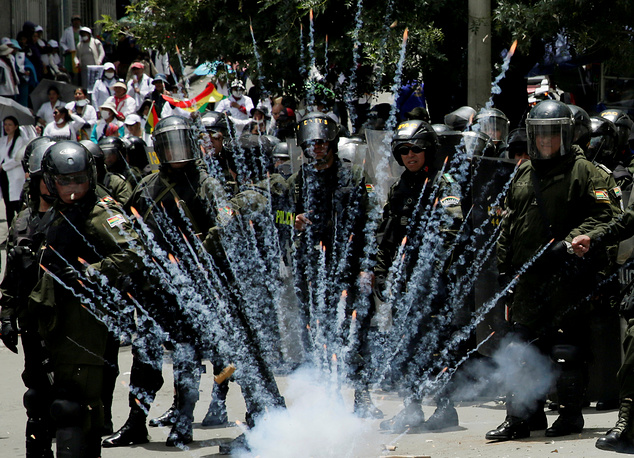 A firecracker explodes next to riot police officers during a protest rally against Bolivia's government new health care policies in La Paz, Bolivia December 27