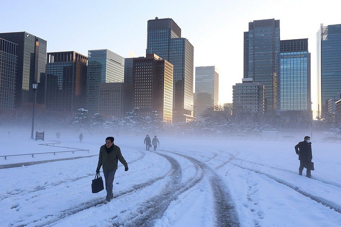 Morning commuters walk across a snow-covered field on the grounds of the Imperial Palace in Tokyo