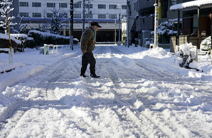 An elderly man crosses a road covered with snow in Tokyo