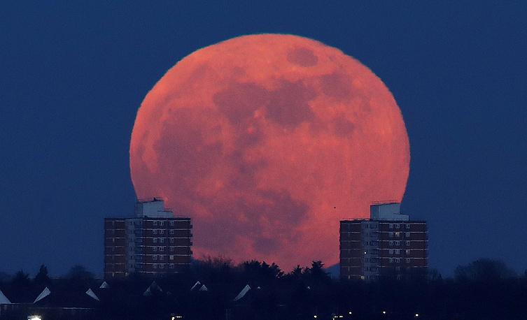 A full moon rises behind blocks of flats in north London, Britain