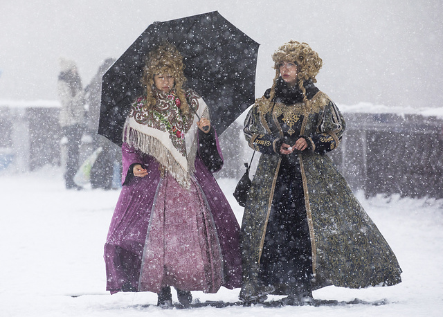 Women in historical costumes walk under a snowfall on Moscow's Sparrow Hills