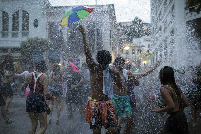 """People cool off in water during the """"Escravos da Maua"""" block party, as part of pre-Carnival celebrations in Rio de Janeiro"""