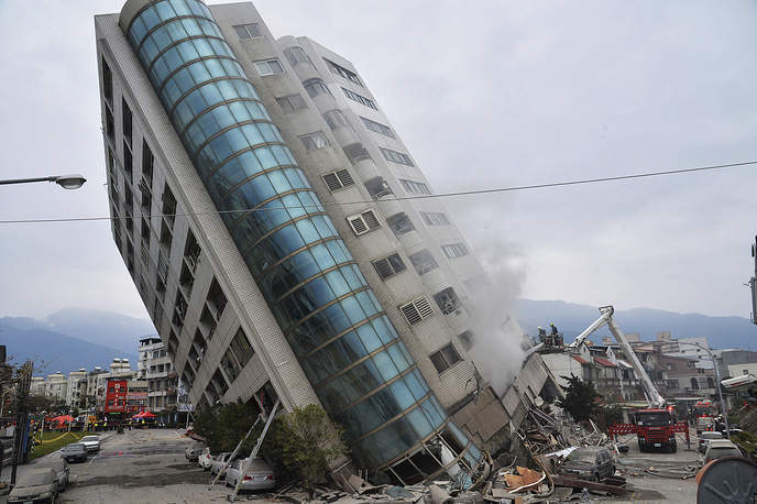 A residential building leans on a collapsed first floor following an earthquake in Hualien