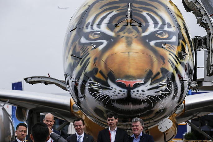 Visitors pose for a photo with the tiger-painted nose of an Embraer E-190 E2 commercial jet parked at the static display area during the 2018 Singapore Airshow