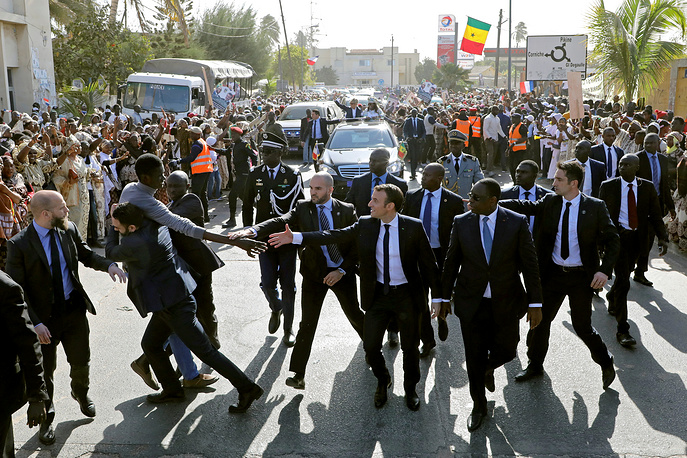 Members of security services react as a man in the crowd tries to shake hands with French President Emmanuel Macron, who walks next to Senegalese President Macky Sall in a street of Saint-Louis, Senegal, February 3