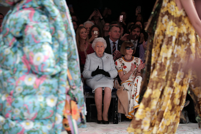 Britain's Queen Elizabeth sits next to fashion editor Anna Wintour as they view Richard Quinn's runway show before presenting him with the inaugural Queen Elizabeth II Award for British Design at London Fashion Week's BFC Show Space in central London, February 20