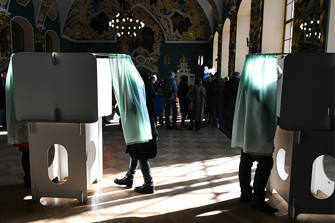 People seen in voting booths during the 2018 Russian presidential election at a polling station at Moscow's Kazansky railway station, Russia, March 18