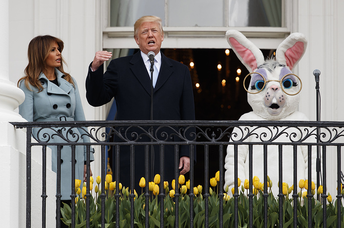 US President Donald Trump, flanked by the Easter Bunny and First Lady Melania Trump, speaks from the Truman Balcony of the White House during the annual Easter Egg Roll in Washington, DC, USA, April 2