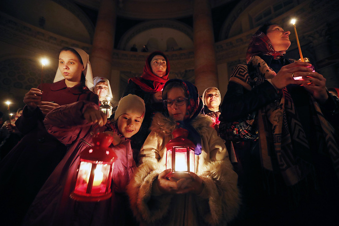 Russian people hold candles lit from the Holy Fire from Jerusalem during Easter church service in Moscow