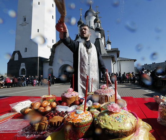 A Russian Orthodox priest sprinkles Holy water as he blesses Easter food and believers prior to the Orthodox Easter holiday celebration at the Church of St. Apostle Peter in St. Petersburg
