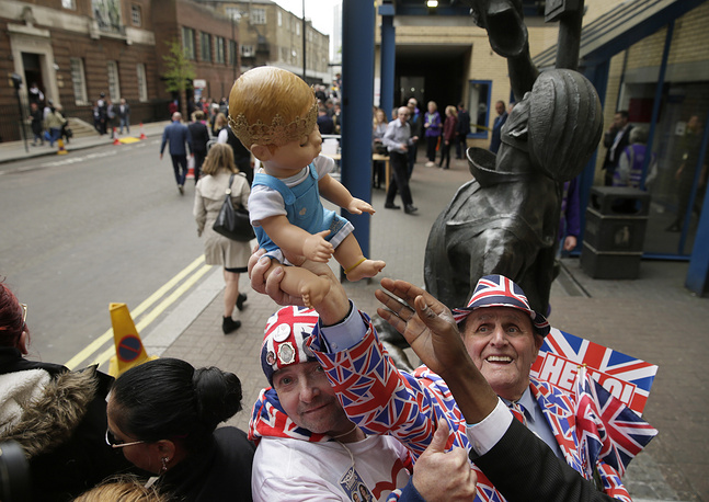 Royal fans pose holding a baby doll opposite the Lindo wing at St Mary's Hospital in London. Kensington Palace says the Duchess of Cambridge has given birth to her third child, a boy weighing 8 pounds, 7 ounces (3.8 kilograms)