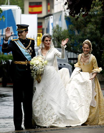 Spanish Crown Prince Felipe and Princess Letizia wave to well wishers as they arrives at the Basilica of Atocha to place the bridal bouquet after their wedding in Madrid, May 22, 2004