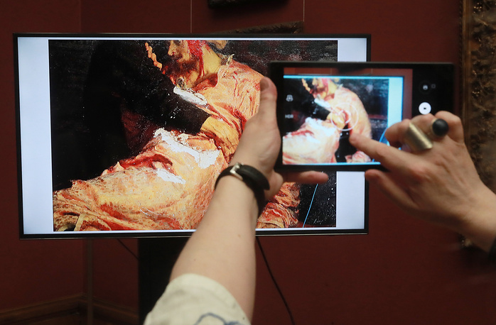 A screen shows Ilya Repin's painting Ivan the Terrible and His Son Ivan, damaged by a man on May 25, 2018