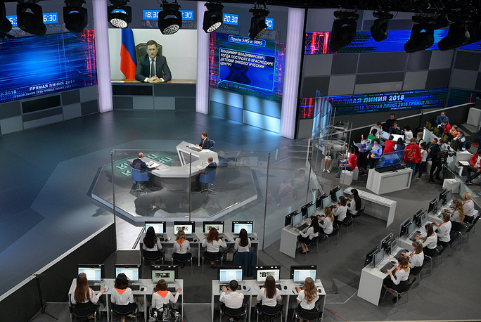 VGTRK TV anchor Andrei Kondrashov, Russia's President Vladimir Putin, and Channel One Deputy General Director and TV host Kirill Kleimenov speak with Russia's Energy Minister Alexander Novak (on a screen)