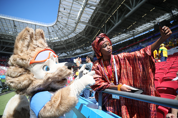 A French fan poses with a person dressed as Zabivaka the Wolf, the official mascot, in her team's 2018 FIFA World Cup Group C Round 1 match against Australia at Kazan Arena Stadium