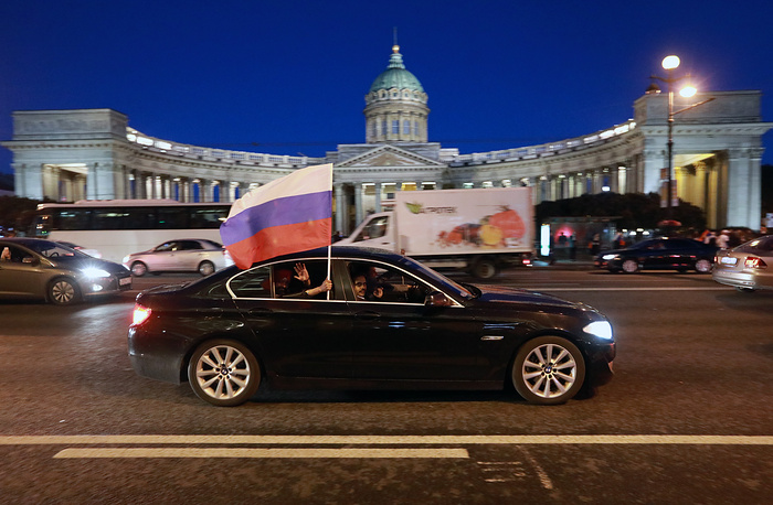 Russian football fans drive past the Kazan Cathedral as they celebrate their team winning in St Petersburg