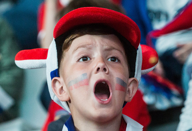 Football fan watching a live broadcast of the 2018 FIFA World Cup Group A match between Uruguay and Russia
