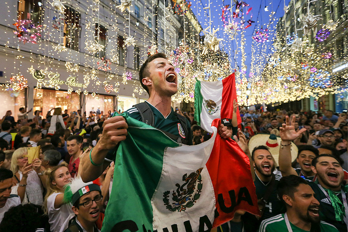 Mexican football fans gather in Nikolskaya Street in central Moscow to celebrate Mexico's victory group F match against Germany