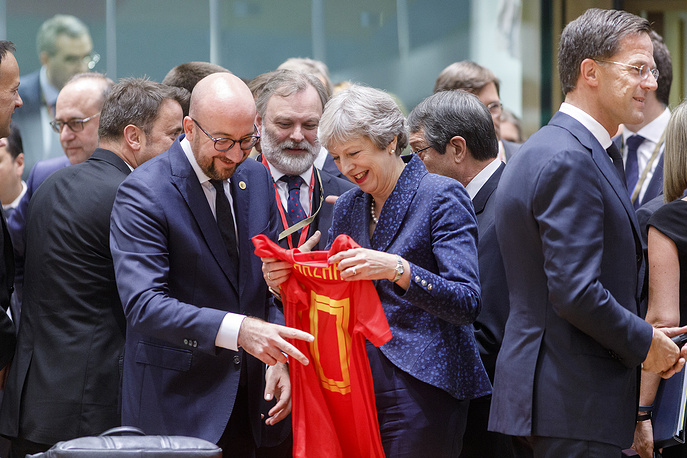 Belgium Prime Minister Charles Michel is giving a T-shirt of Belgium national football team to the Prime Minister of the United Kingdom Theresa May during EU summit in Brussels, June 28