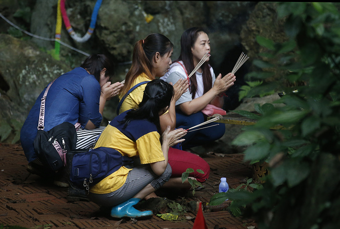 Family members pray near the cave where 12 boys and their coach have been trapped since June 23 in northern Thailand