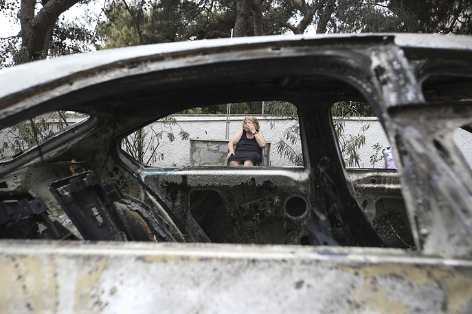 A woman sits outside her burned house in Mati east of Athens