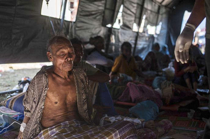 An elderly man rests in a makeshift hospital after surviving a major earthquake in Kayangan on Lombok Island