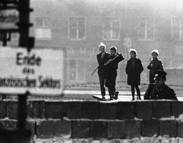 """East Berlin youngsters with toy guns play at being """"people's police"""" as they look over the concrete wall in the Bernauer Strasse, 1961"""