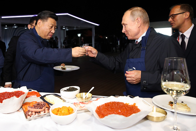 President Vladimir Putin and his Chinese counterpart Xi Jinping eating Russian pancakes at the Far East Street exhibition on the sidelines of the 2018 Eastern Economic Forum on Russky Island, September 11