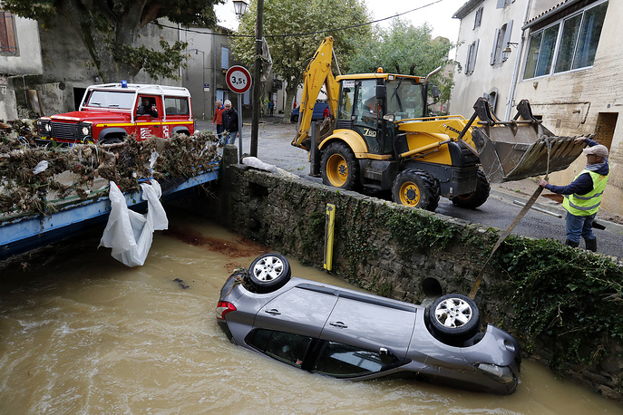A man using a digger remove a car out of water in Villegailhenc, France