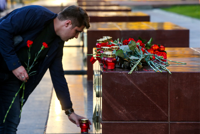 A man leaves flowers at the Great Patriotic War Hero City of Kerch monument in Moscow's Alexander Garden, for the victims of the 17 October 2018 Kerch polytechnic school attack
