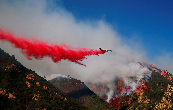 An aircraft drops flame retardant as firefighters battle the Woolsey Fire as it continues to burn in Malibu, California, November 11