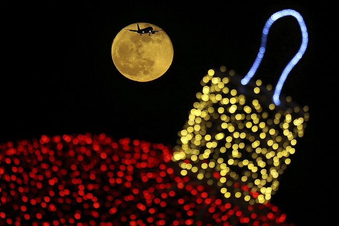 The moon shines behind a decorated with an illuminated Christmas ornament as an aircraft prepares for landing at the airport in southern coastal city of Larnaca In the eastern Mediterranean island of Cyprus, December 23