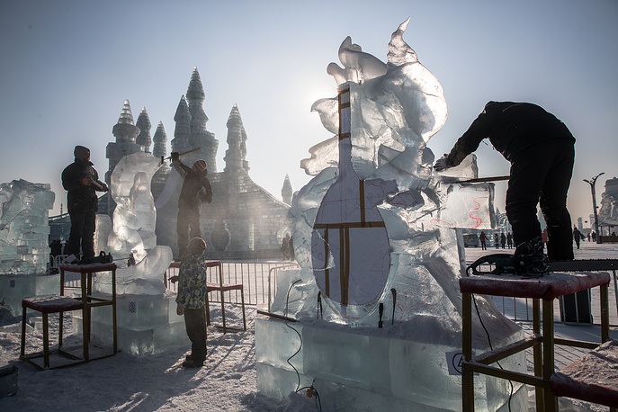 Participants carve their ice sculptures in Harbin
