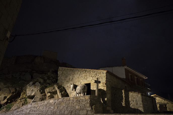 On the eve of Saint Anthony's Day, dozens ride their horses through the narrow cobblestone streets of the small village of San Bartolome during the annual Luminarias festival