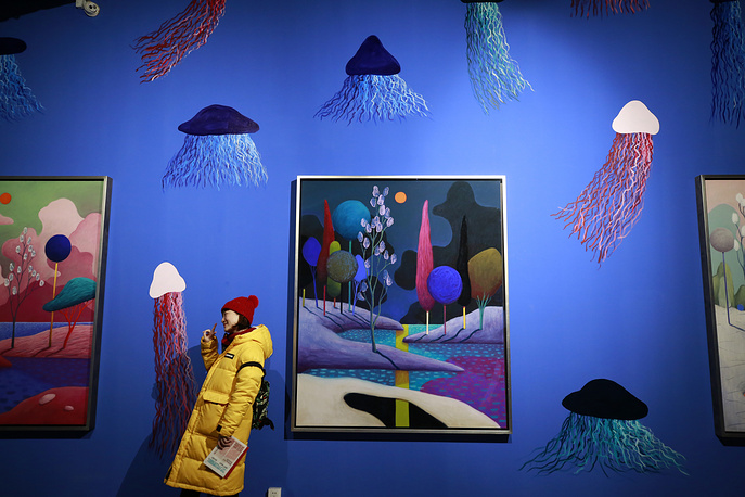 A visitor pose for pictures in front of artworks by Swiss artist Nicolas Party in his exhibition titled 'Arches' at M WOODS gallery in Beijing, January 16